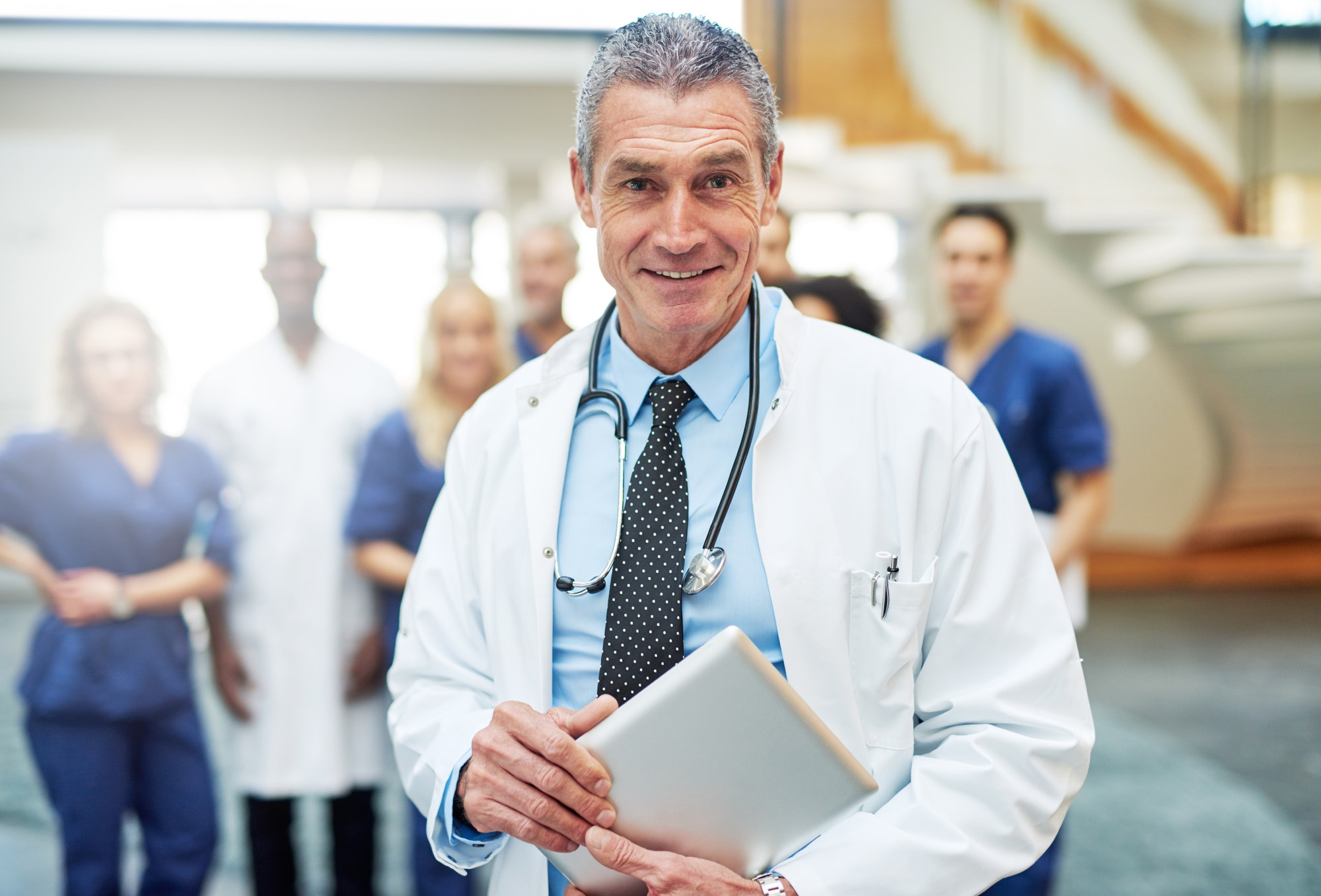 Cheerful mature doctor with tablet in hospital