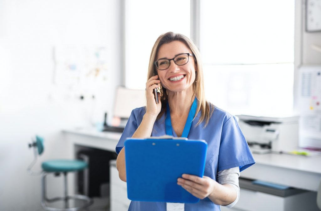 A portrait of dental assistant in modern dental surgery, using smartphone