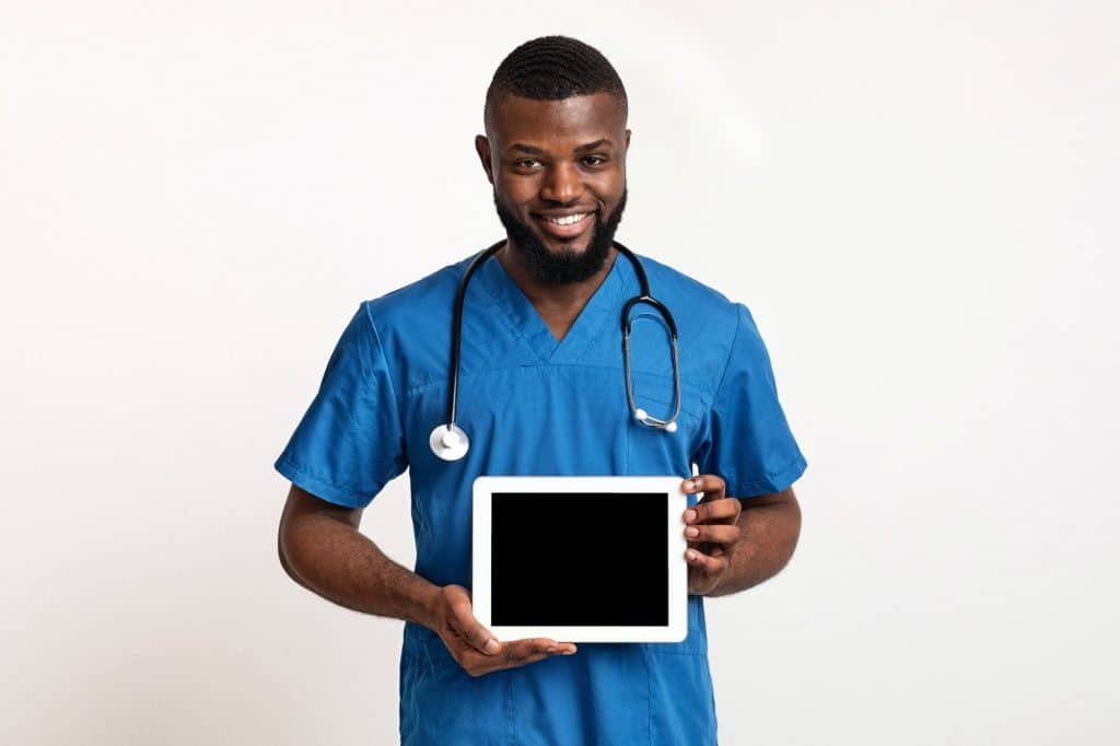 Black friendly doctor demonstrating empty digital tablet screen