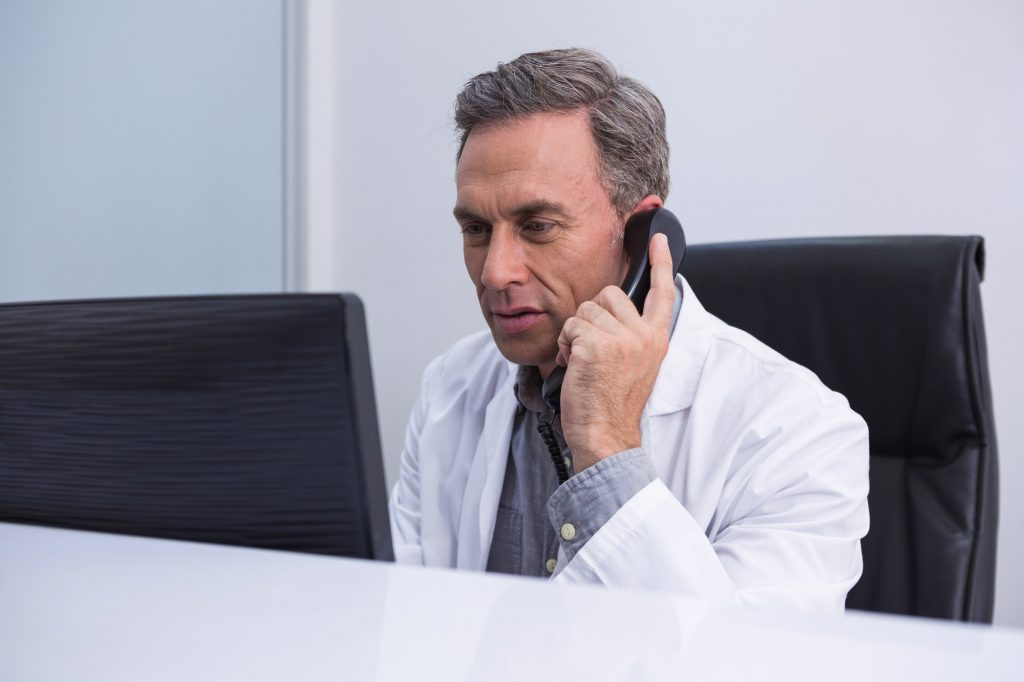 Dentist talking on phone while sitting by computer