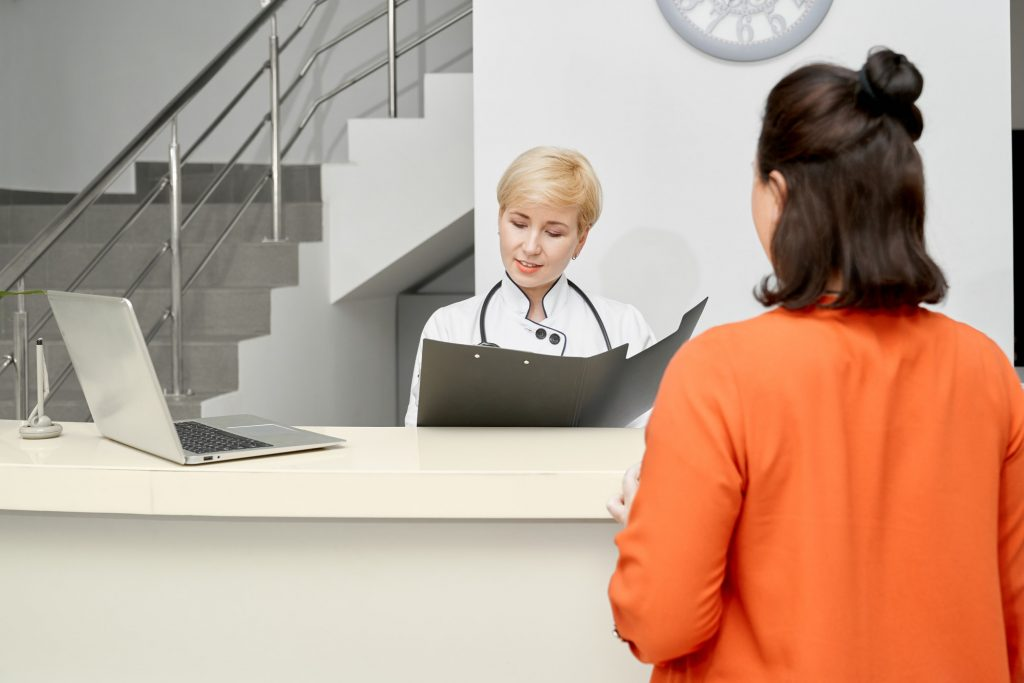 Patient and doctor with folder on reception
