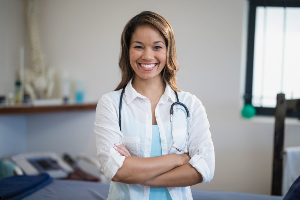 Portrait of smiling young female therapist standing with arms crossed