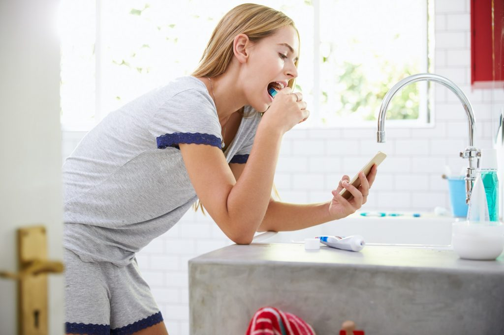 Woman In Pajamas Brushing Teeth And Using Mobile Phone