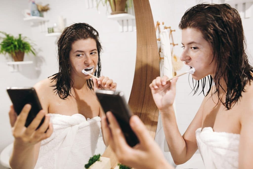 Young happy woman in white towel brushing teeth and looking at smartphone