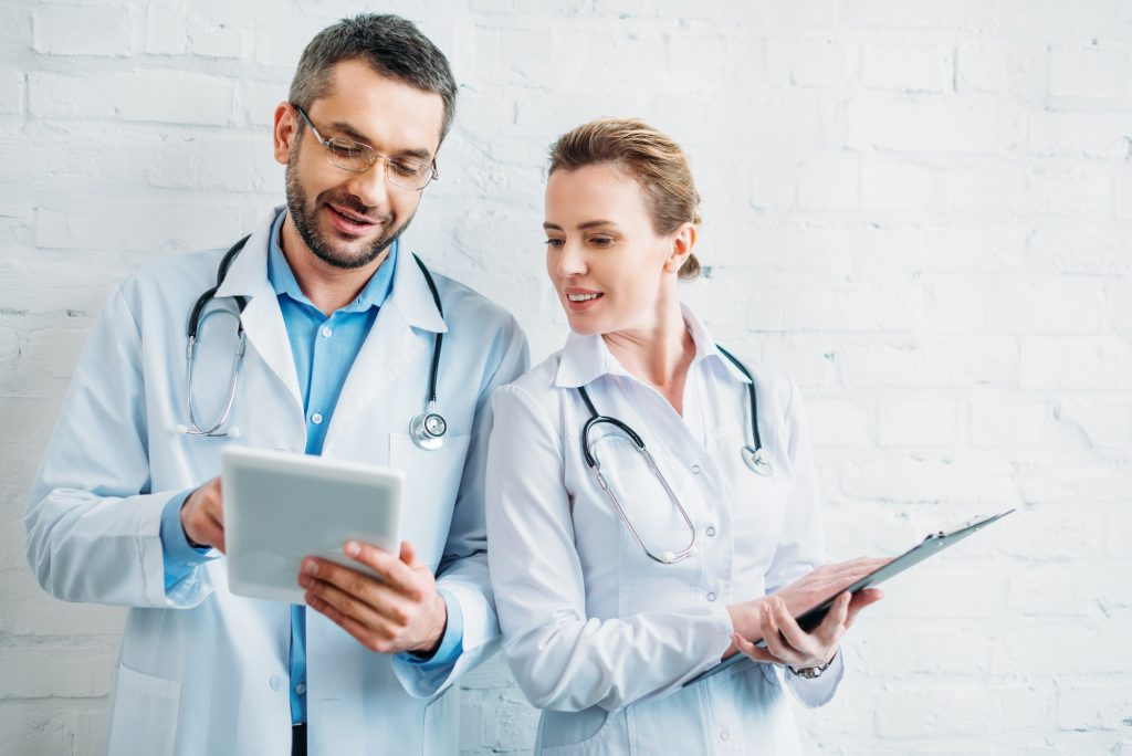 happy doctors working together with tablet and clipboard