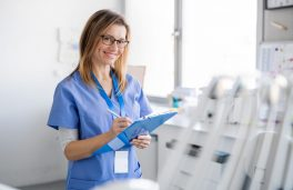A front view portrait of dental assistant in modern dental surgery, looking at camera.