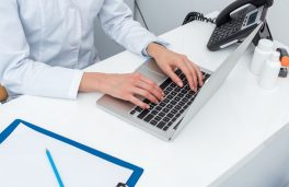 cropped shot of female doctor using laptop at workplace