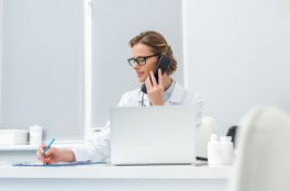 female doctor talking by phone and writing in clipboard at workplace