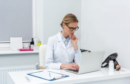thougtful young female doctor using laptop at workplace
